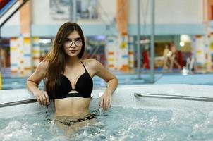 het mooie meisje zit in het zwembad