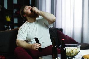 gelukkig dikke man eet popcorn liggend op de bank voor een tafel met bier