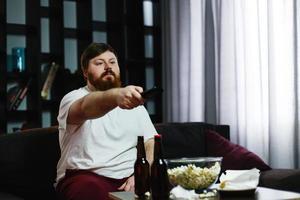 gelukkige dikke man zit op de bank en kijkt tv met popcorn en bier