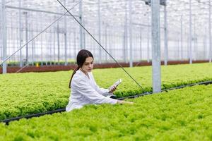 vrouwelijke onderzoeker die planten in het Greeen House bestudeert
