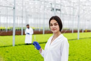 vrouwelijke onderzoeker houdt een glazen buis vast