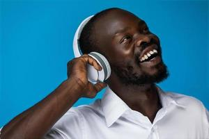 lachende Afrikaanse man geniet van het luisteren naar muziek