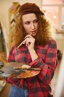 kunstenaar houdt een penseel vast en denkt aan haar werk