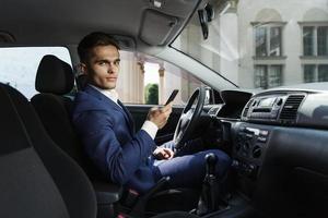 lachende zakenman zit in de auto en werkt met zijn smartphone