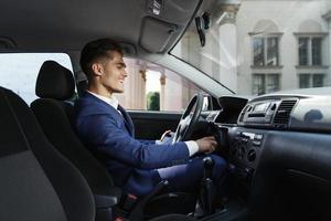 lachende zakenman zit in de auto