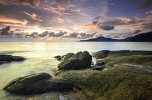 zonsopgang op rotsachtig strand in terengganu, maleisië. foto