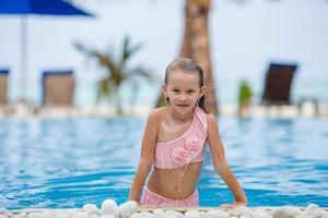 glimlachend gelukkig meisje met plezier in het buitenzwembad