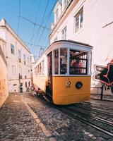 gele en witte tram die de heuvel opklimt foto