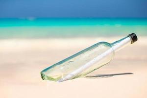 glazen fles met een bericht erin op een strand foto