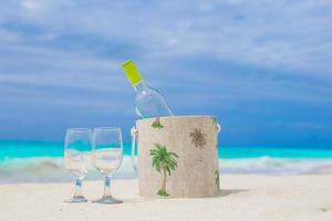 fles witte wijn en twee glazen op het strand foto