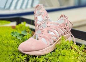 roze vrouw sportschoenen op de groene plant foto