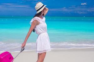 vrouw die met haar bagage op een strand loopt