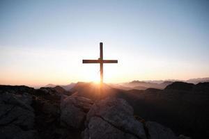 kruis op een berg bij zonsondergang foto
