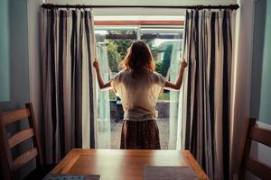 jonge vrouw die de gordijnen opent bij zonsopgang