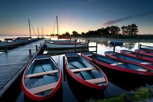 rode boten op haven bij zonsopgang foto