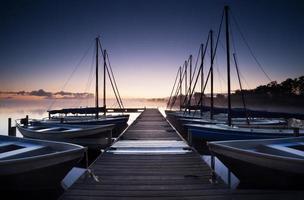 pier en jacht op meer bij zonsopgang foto