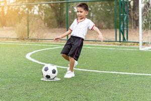 kleine jongen te voetballen foto