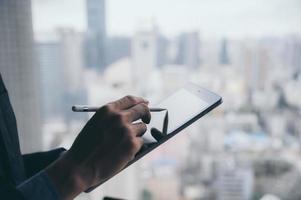 zakenman die met tablet werkt met de achtergrond van de stad