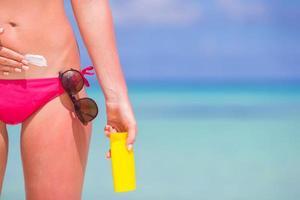 vrouw zonnebrandcrème zetten op een strand foto