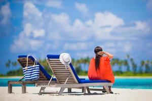 vrouw zittend op een stoel op een strand
