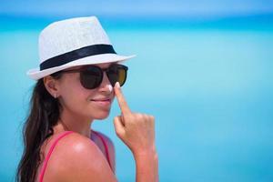 vrouw zonnebrandcrème op haar neus toe te passen foto
