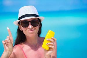 vrouw zonnebrandcrème op haar neus zetten foto