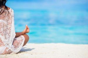 vrouw mediteren op een strand met kopie ruimte foto