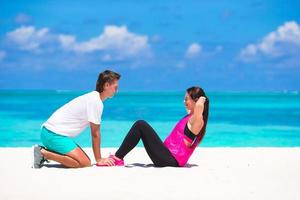 man vrouw spotten tijdens het doen van crunches op een strand