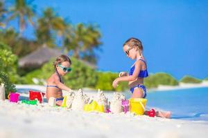 twee meisjes die een zandkasteel bouwen foto