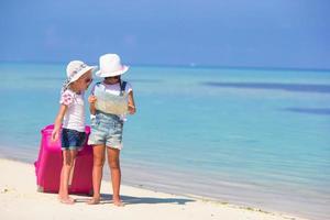 twee meisjes met een kaart en bagage op een strand
