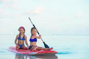 twee meiden die plezier hebben met paddleboarding foto
