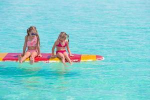 twee meisjes zittend op een surfplank foto