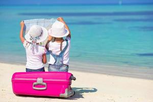 twee meisjes kijken naar een kaart zittend op bagage op een strand