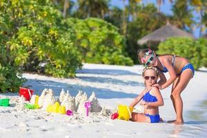 twee meisjes spelen in het zand op een strand foto