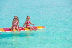 twee meisjes op een surfplank foto