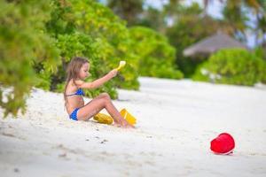 meisje zand scheppen op een strand foto
