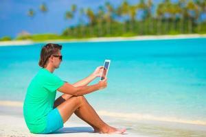 man met een tablet op een tropisch strand