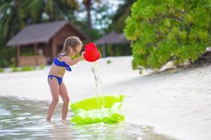 Maldiven, Zuid-Azië, 2020 - Meisje speelt in het water op een strand foto
