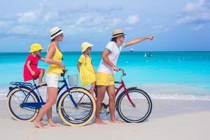 familie fietsen op een tropisch strand foto