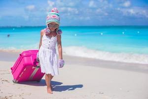 meisje met winter hoed en wanten wandelen met bagage op een strand