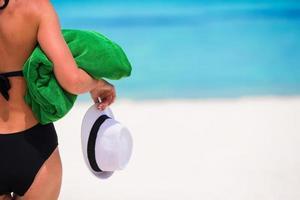 vrouw met groene handdoek en een hoed op een wit strand