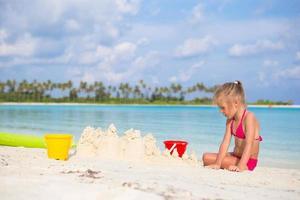 meisje bouwt een zandkasteel op een strand foto