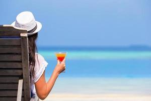 vrouw met een cocktailglas in de buurt van zwembad