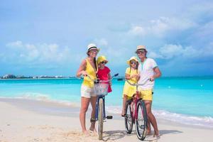 familie op strand met fietsen foto