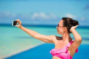 vrouw die een selfie neemt bij een zwembad foto