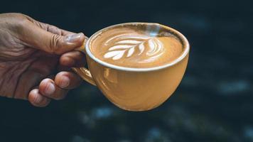 hand met een latte in een gele mok