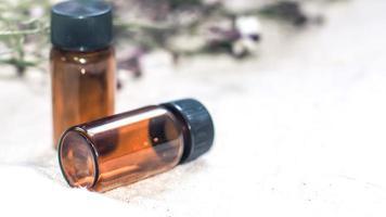 flesje etherische olie. kruidengeneeskunde of aromatherapie druppelflesje geïsoleerd op een witte achtergrond. verse rozemarijnbloemen en etherische oliën op tafel foto