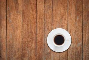 bovenaanzicht van witte koffiekopje op houten achtergrond