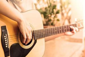 close-up van persoon die een akoestische gitaar speelt