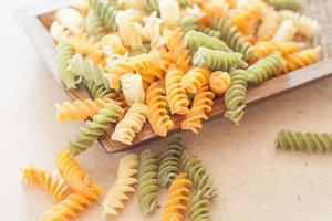 rauwe fusilli pasta op een houten dienblad foto